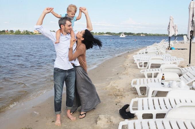 海ではしゃぐ若い夫婦とかわいい子供